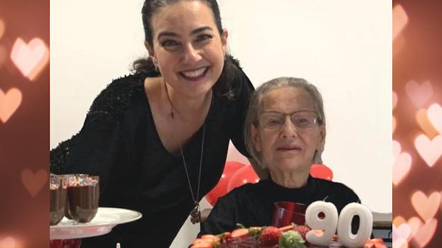 Mulher jovem abraça mulher idosa, em frente a bolo de aniversário