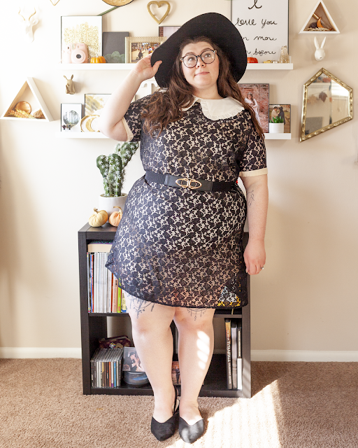 An outfit consisting of a black wide brim hat, a peter pan collar with ruffles over a black lace dress with a beige lining and black pointed toe flats.