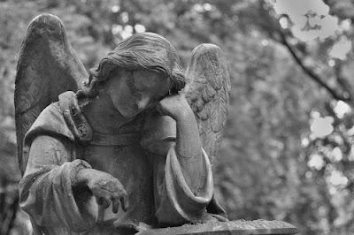 Estátua de pedra no cemitério. #PraCegoVer