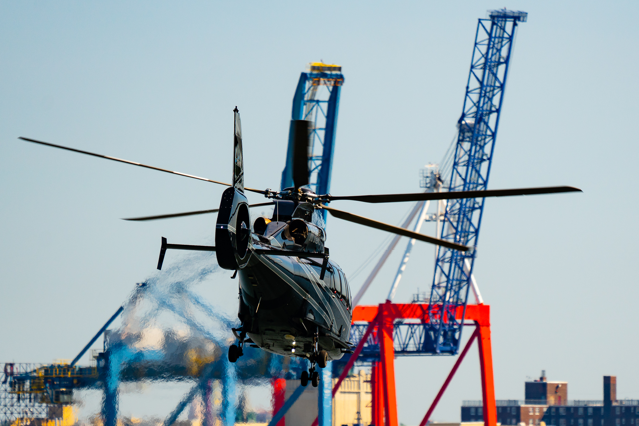 a photo of a black helicopter taking off in new york city