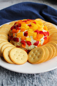 havarti cheese ball coated in diced red, yellow and orange bell pepper and circled by crackers on a plate