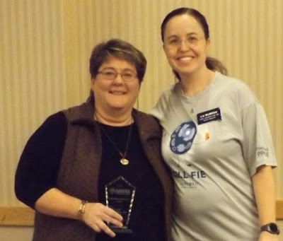Judy Vondruska holding award, standing next to Liz McMillan