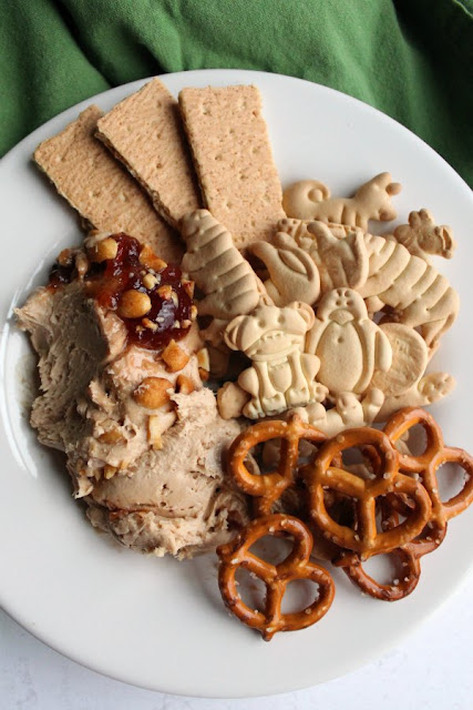 small plate filled with peanut butter and jelly dip, animal crackers, pretzels and graham crackers