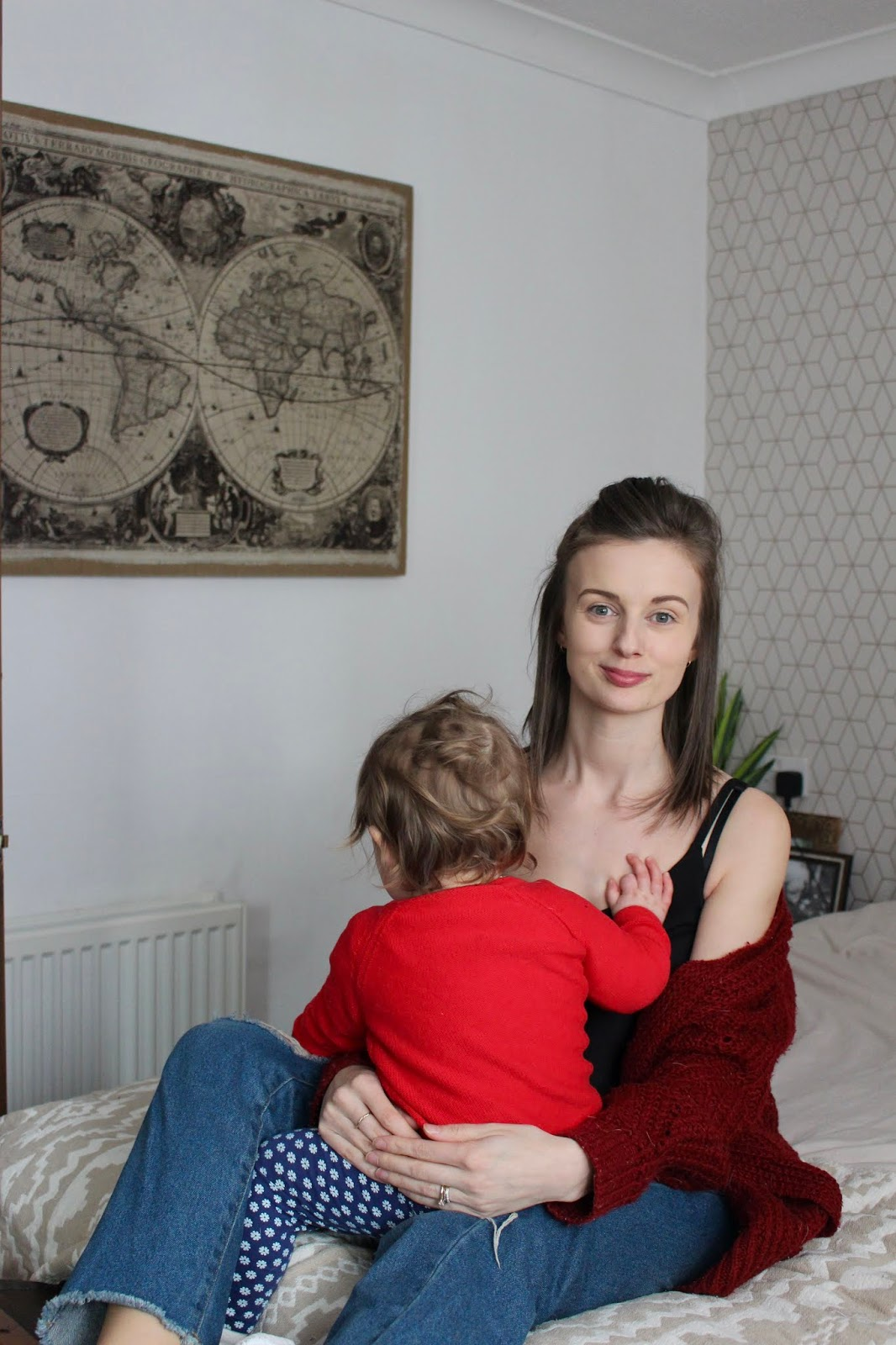Lifestyle image of mother and baby sat on bed.