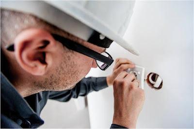 An electrician with a helmet working on a plug in a wall.