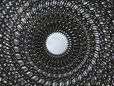 photo of a spiral shaped structure, looking up to a hole to the sky
