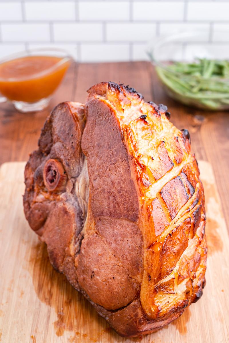 Photo of Keto Apricot Bourbon Glazed Ham on a wooden cutting board.