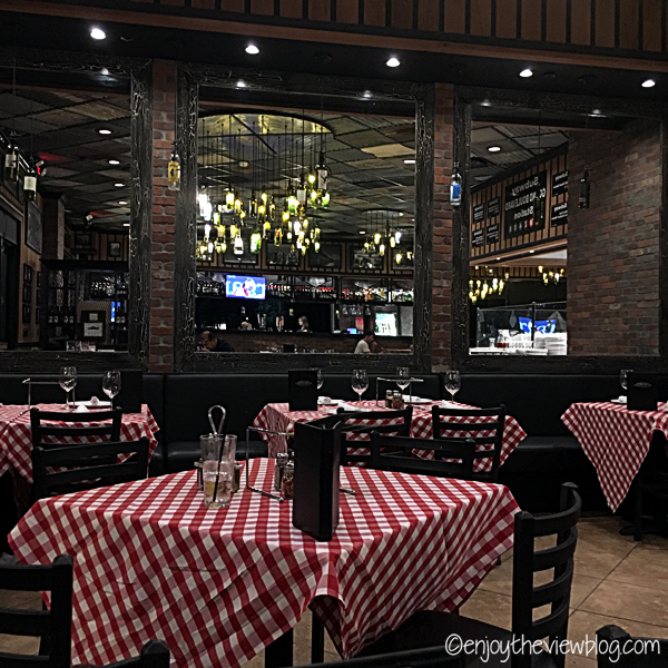 interior of Grimaldi's Miramar Beach - tables and chairs with red & white checked tablecloths, brick walls, tin ceiling, wine bottle chandeliers