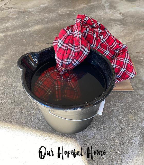flannel shirt in bucket bleach water