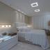 Quarto com cores claras e móvel em ônix iluminado integrado ao banheiro por cortina!