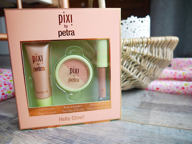 a peach box containing a tube of peach highlighter, a green tub with half gold highlighter and half pink, and a light peach lipgloss with green lid