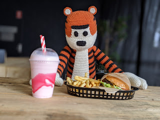 Crochet Hobbes (tiger) plushie sitting at a restaurant table with a pink milkshake, burger and fries in front of him.