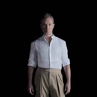 Gary Kemp in a white shirt and beige chinos against a black background