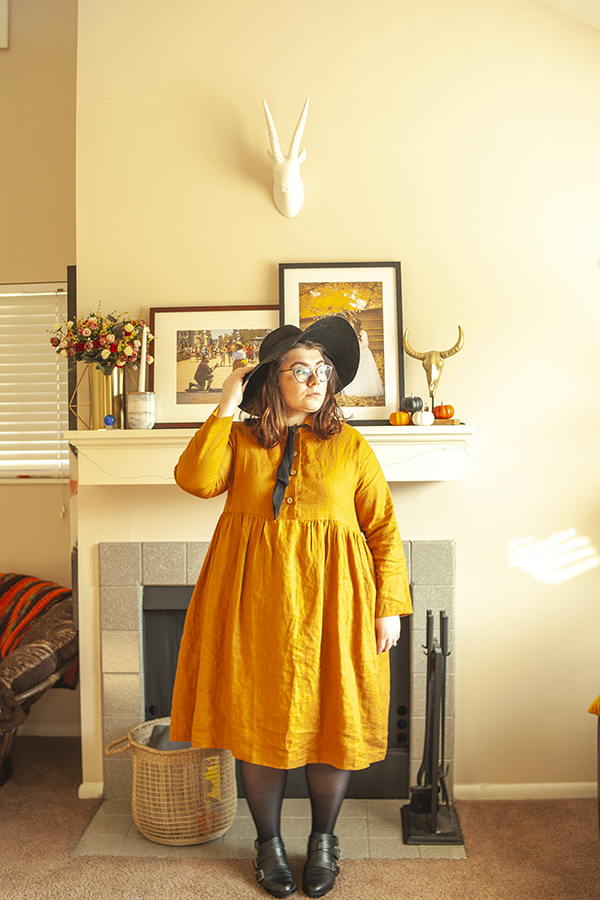 An outfit consisting of oversized black hat, yellow collared linen babydoll dress, sheer tights and black Chelsea boots.