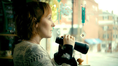 Love in Kilnerry 2019 indie movie still featuring Kathy Searle looking out a window with binoculars