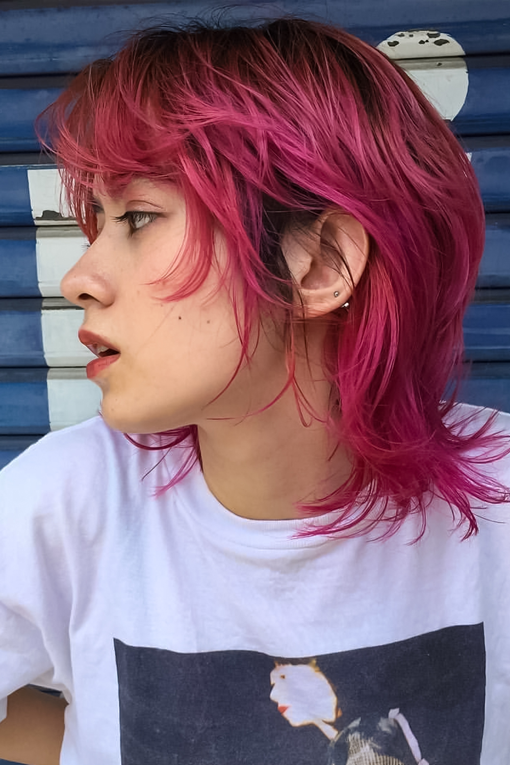 woman with dyed edgy mullet haircut is posing