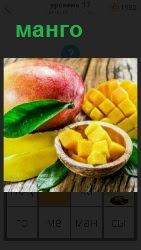 плод манго и порезанный на кусочки в тарелке