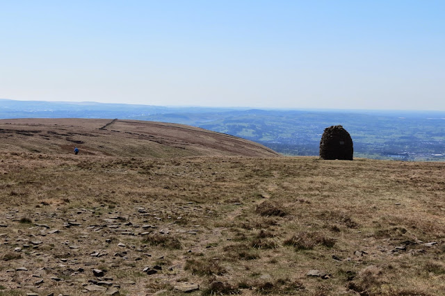 A tall, cylindrical rock cairn silhouetted against the edge of the hilltop.