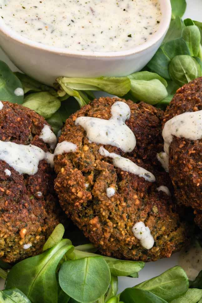 Close up photo of 3 falafel discs with vegetables and vegan yoghurt sauce