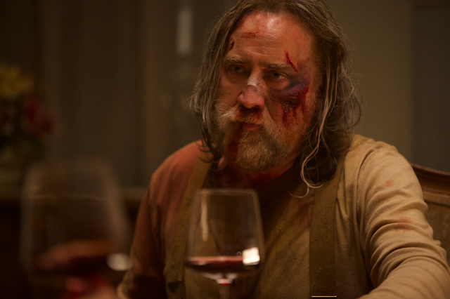A very bloody bearded man sits at a table