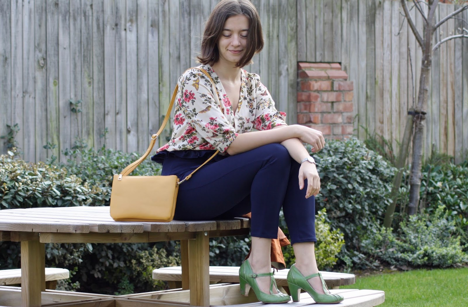 Abbey, smiling, sits on wooden picnic table, wearing a floral top, blue trousers, yellow bag, and green shoes