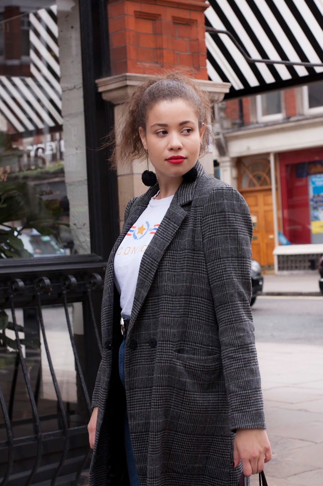 Eboni wearing grey check coat, black pom pom earrings and red lipstick