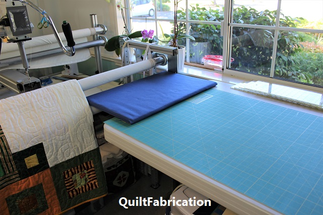 cutting table and Innova quilting machine in QuiltFabrication's studio
