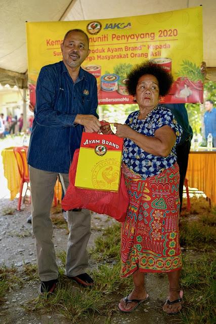 Villagers (right) in Kampung Orang Asli Kangkar Senanga receiving 1 month canned food supply from Ayam Brand