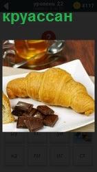 На столе на салфетке лежит кондитерское изделие круассан и шоколадные плитки и чашка с чаем