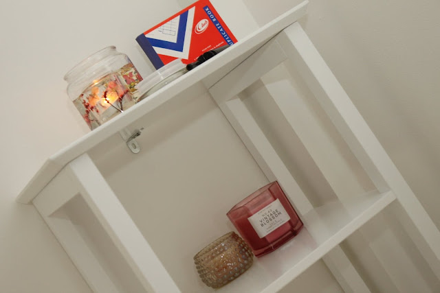 Candles and other small accessories on a shelving unit in the treatment room.