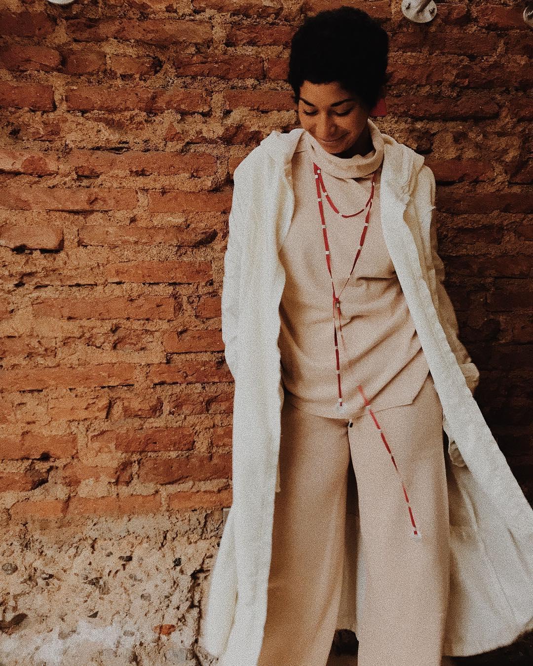 Tenida de beatle y pantalón beige con abrigo blanco y collar rojo de Mercado Moderno Valparaíso
