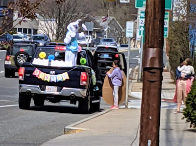 The Easter Bunny stands in a truck facing a parent and child on the sidewalk and greets them.