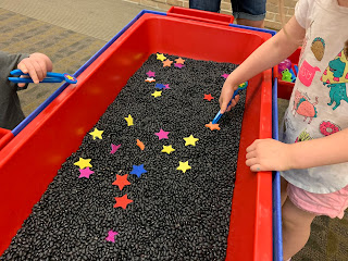 kids using tweezers to catch the colorful foam stars in the bin of dried black beans