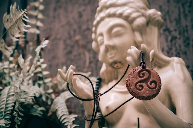 colar triskle de cerâmica na mão de deusa hindu