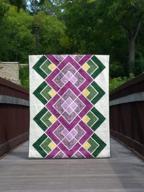 Purple and green geometric quilt on a footbridge