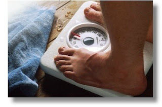image of employee on scale weighing self as part of new year's resolution t lose weight