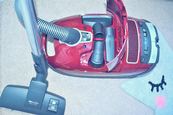 Miele Complete C3 Pure Red Bagged Cylinder Vacuum Cleaner showing the three additional tools stored under the hood