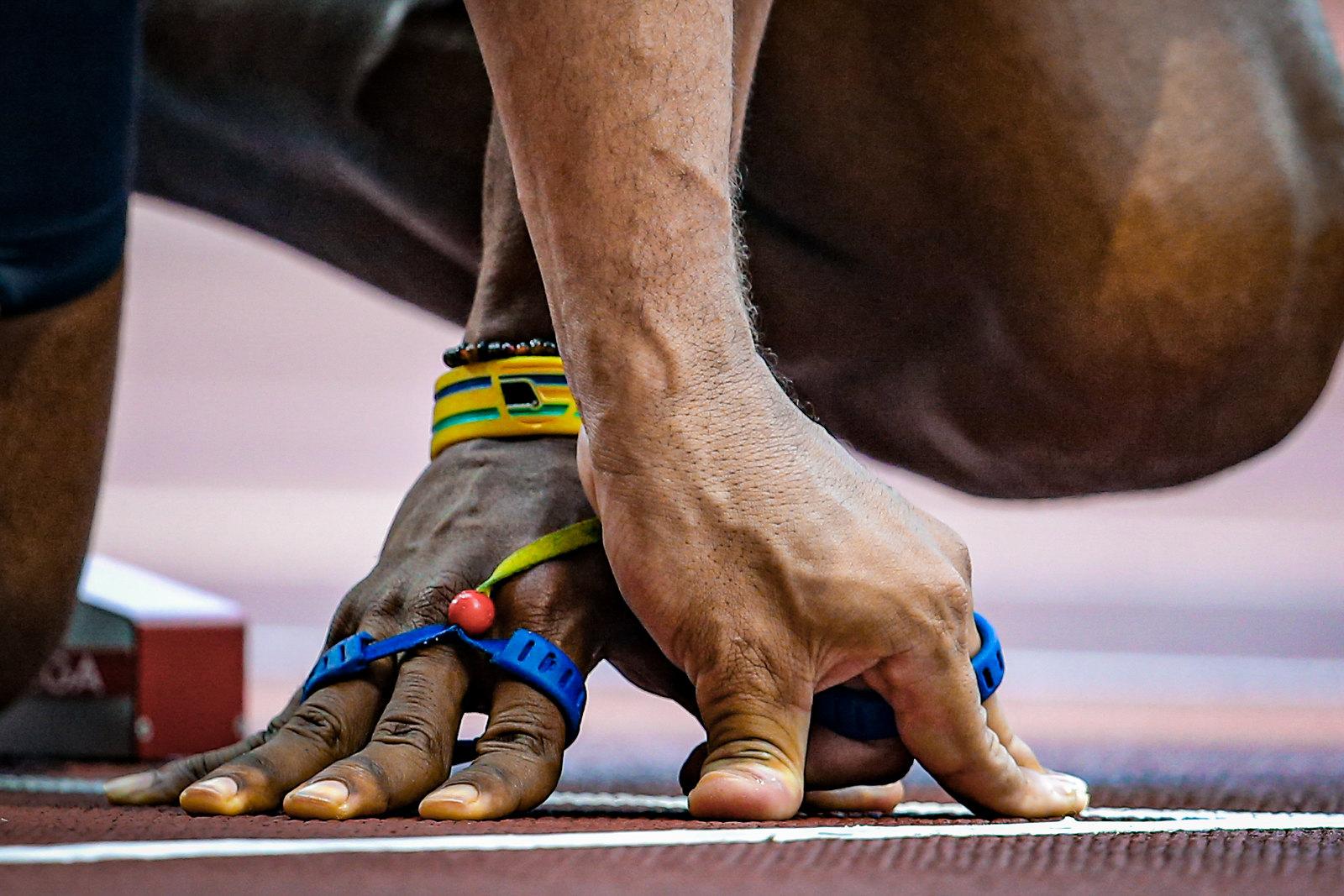 mão de atleta e guia entrelaçadas por fita no chão do estádio olímpico