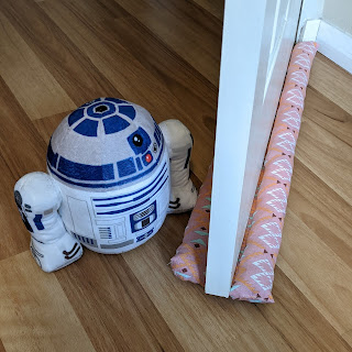 An ajar door with double snake on either side of the base, beside a plushie R2D2 door stop.