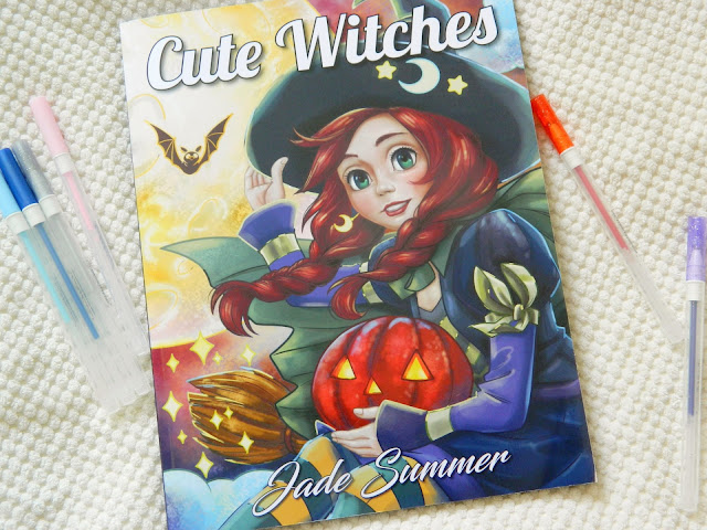 A photo showing a colouring book featuring an illustration of a witch holding a jack-o-lantern. Cute Witches by Jade Summer