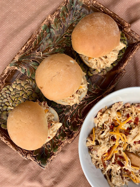 Creamy ranch chicken is slow cooked and topped with bacon and cheese on slider sized rolls for a delicious family pleasing meal.