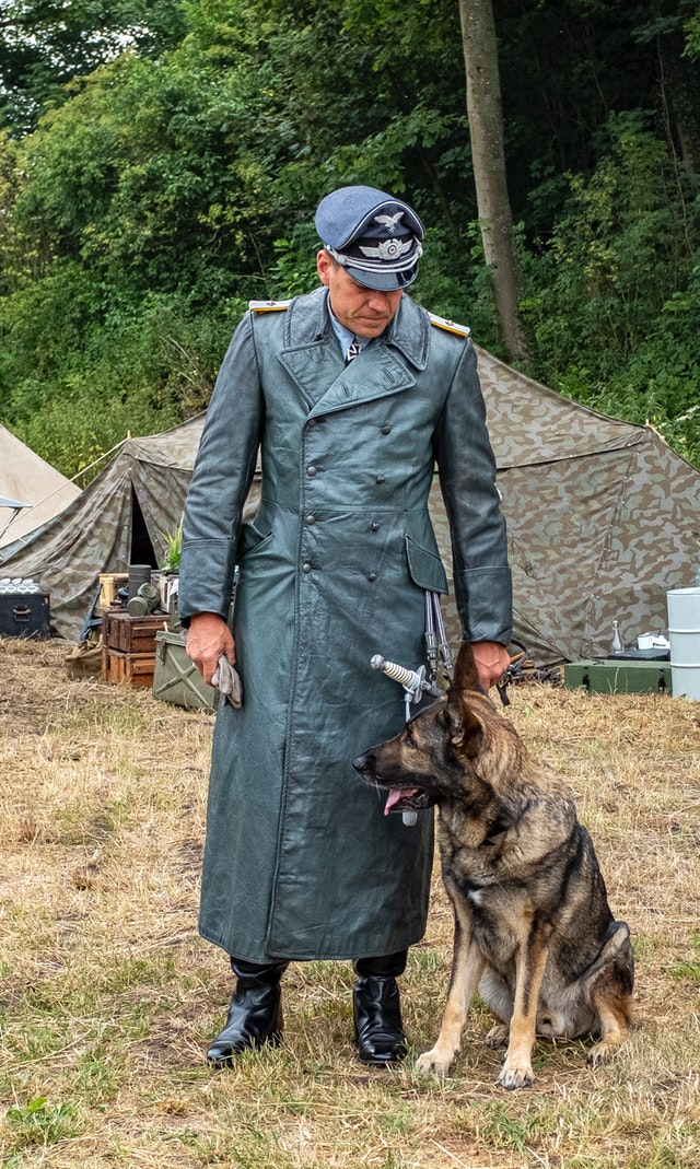 photo-of-man-in-old-military-uniform-standing-next-to-german-shepherd