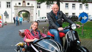 Die Moderatorin Tamina Kallert sitzt im Beiwagen eines Motorrads, auf dem Joe Bausch sitzt.