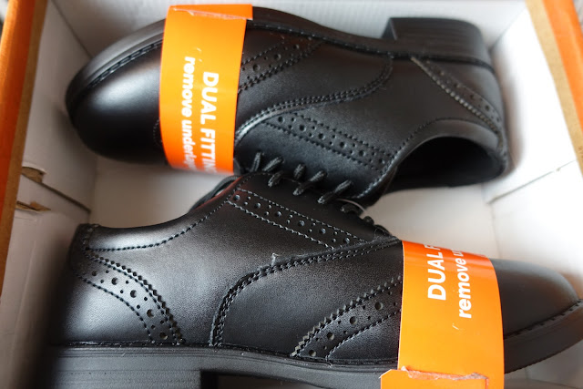 Black school shoes laid in box
