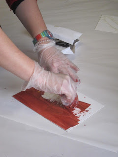 Photograph of artist adding ochre-coloured ink to printing board in preparation for making a print