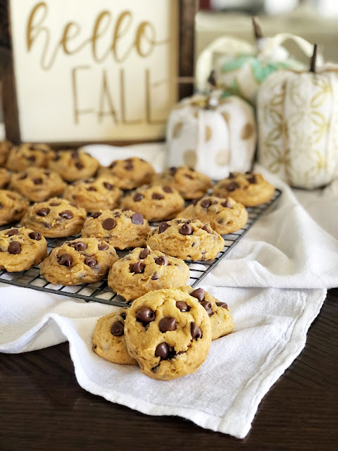 pumpkin chocolate chip cookies on a cooling rack with fall decor behind