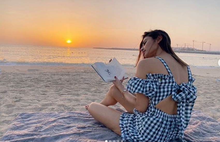 mouni-roy-reading-book-on-beach