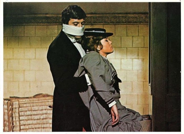 Oliver Reed wearing a mask and carrying an unconscious Diana Rigg in The Assassination Bureau