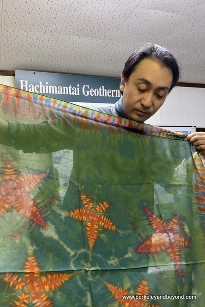 instructor holds sample tie-died cloth with starfish design at Geocolor:  Hachimantai Geothermal Dyeing in Hachimantai city, Japan