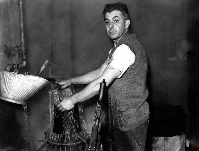 A worker at a Connecticut hat manufacturing plant treating a hat under water